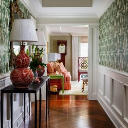 In this hallway the dark wood floors and green patterned wallpaper is a tribute to Autumn.