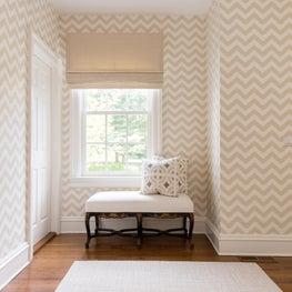 Neutral chevron wallpaper in this hallway juxtaposes the dark wood floors.