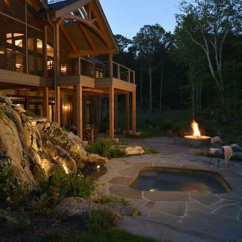 A terraced spa area set against the backdrop of a waterfall and campfire pit.