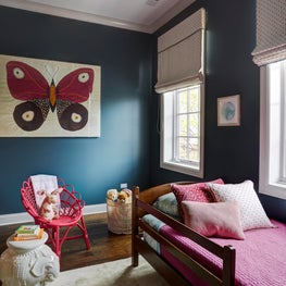 Girls room with butterfly artwork, pink and dark teal with cream rug