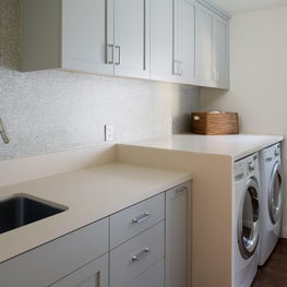 Modern laundry room with a grey penny tile backsplash
