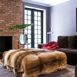 Family Room with brick fireplace, purple walls, and cement floor tiles