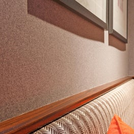 Grey flannel walls in bar w/ custom zebra upholstered bench by Sophia Shibles