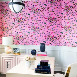 Home office with navy painted ceiling and bold, pink floral wallpaper