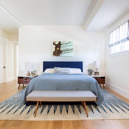 Oceanic blues inspire contemporary warmth in this light and bright master bedroom. The plush area rug's bold graphic design anchors the space. A collection of paintings by Ruben Vincent adds contemporary form and color.