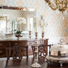 Crystal and silver accents this elegant dining room with patterned wallpaper.
