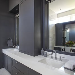 Double sink bathroom w/ sleek white countertops & dark gray cabinets