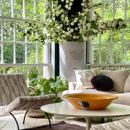 Sun-filled corner of a sunroom seating arrangement with iconic pieces of Midcentury furniture and neutral geometric JIM THOMPSON fabrics.