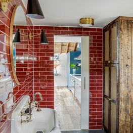BATH WITH GLOSS RED TILES,  CONCRETE FLOORS, RECLAIMED CABINET WITH BRASS MESH