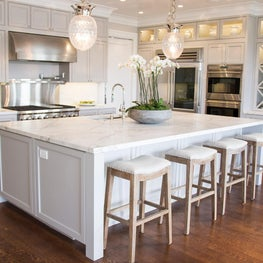 Transitional kitchen with white marble, gray cabinetry, and pineapple pendants.