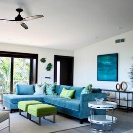 family room/teal velvet sofa/green ottoman/colorful art/dark wood/vacation home