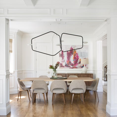 Bright dining room with modern chandelier, midcentury chairs, custom wainscot.