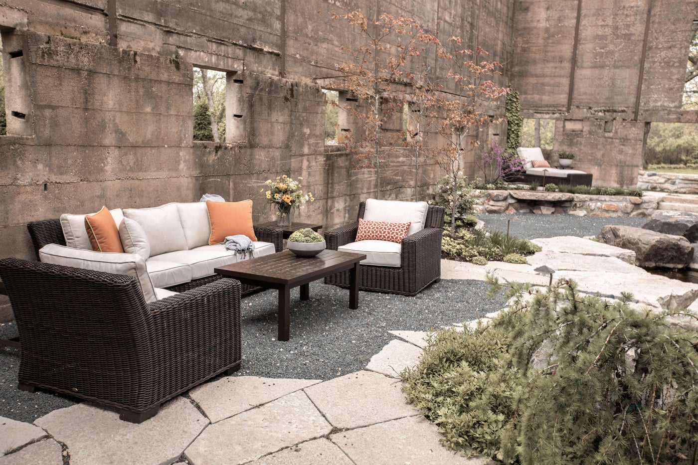 Outdoor woven furniture, orange pillows, linen color cushions, woven arm chairs