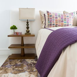 Neutral bedroom with pops of purple, pattern, and texture in Woodlands home