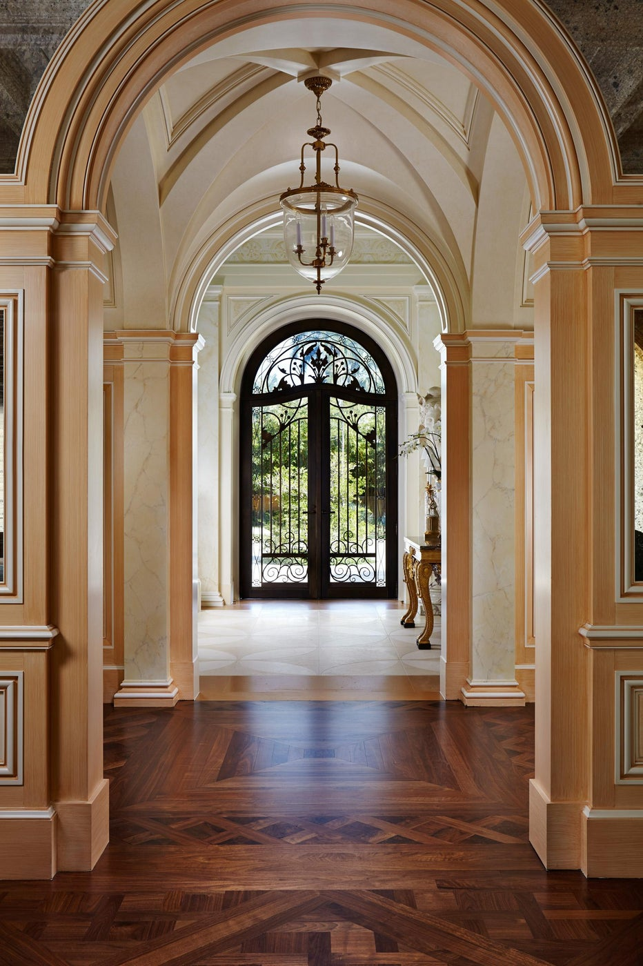 Bronze and glass front door seen across a gallery and entry hall