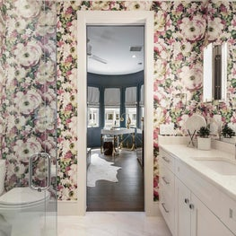 Flowery wallpaper adds a whimsical ambiance to this white powder room.