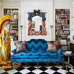 Vintage Americana delights in this antique dealer's secluded city dwelling. Graphic pops range from the signature checkerboard floor to the dazzling Jim Thompson fabrics. Built-in bookcases hold a research library in this historic 1920's carriage house.