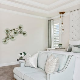 Handblown glass wall art in serene white & mint hued master bedroom w/seating.