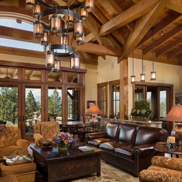 Great room with multi-tiered iron wagon wheel chandelier and wooden beams