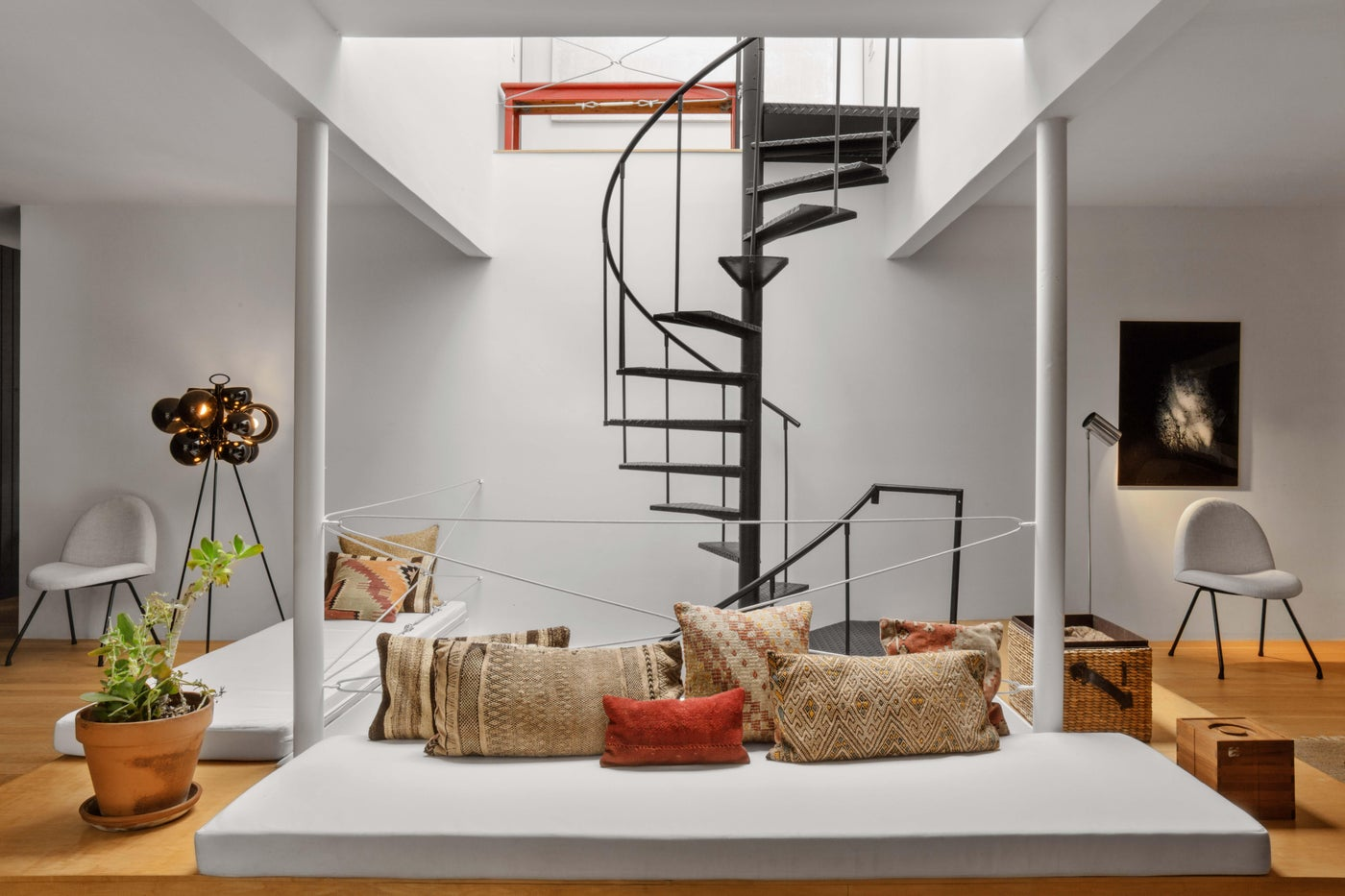 Basement family room with spiral staircase, mid-century pieces in modern space