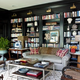 An eclectic seating area with a wall of shelves