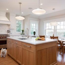 Kitchen bumpout with wood hood, quartz island, Wolf range, and marble backsplash
