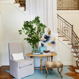 Foyer with iron railing, white two story drapery, entry table & blue leather rug