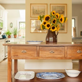 Kitchen in a coastal home features a custom wood console and painted cabinetry