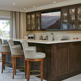 Neutral tones, warm wood cabinetry & water views enhance this relaxed bar area.