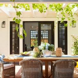 Dining on herringbone brick patio with grapevine trellis, French doors