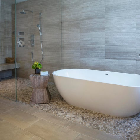 Victoria & Albert soaking tub, river rock on steam shower floor and below tub.