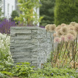 Linear style Bluestone Wall creates a modern accent to the lush gardens