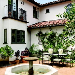 Enclosed courtyard of a Spanish Colonial Revival residence with a fountain