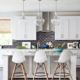 Kitchen with dark black ceramic backsplash, glass pendants counter bar stools
