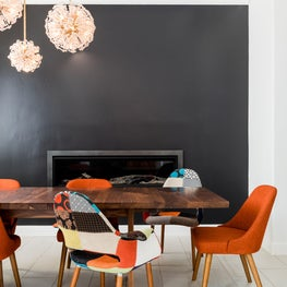 Wooden dining room table with black walls, pendant lights and patchwork chairs
