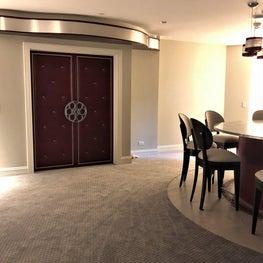 Home theater, red upholstered doors, movie reel door pulls, bar stools