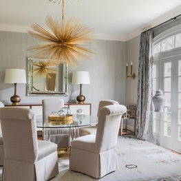 The subtle wall covering in this elegant dining room offsets a striking rug and jewel-like lighting