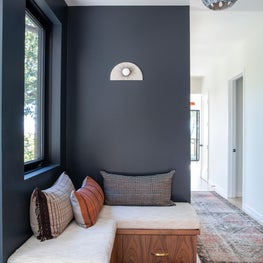 Hallway with built-in banquette and dark blue-grey walls