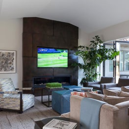 Watch a game, a movie or simply hang out and let the outdoors in this Family Room with custom steel fireplace wall and Nana wall system - Los Altos Hills Residence