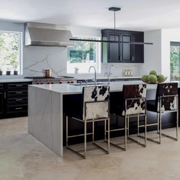 Custom counter stools in contemporary black kitchen with waterfall island