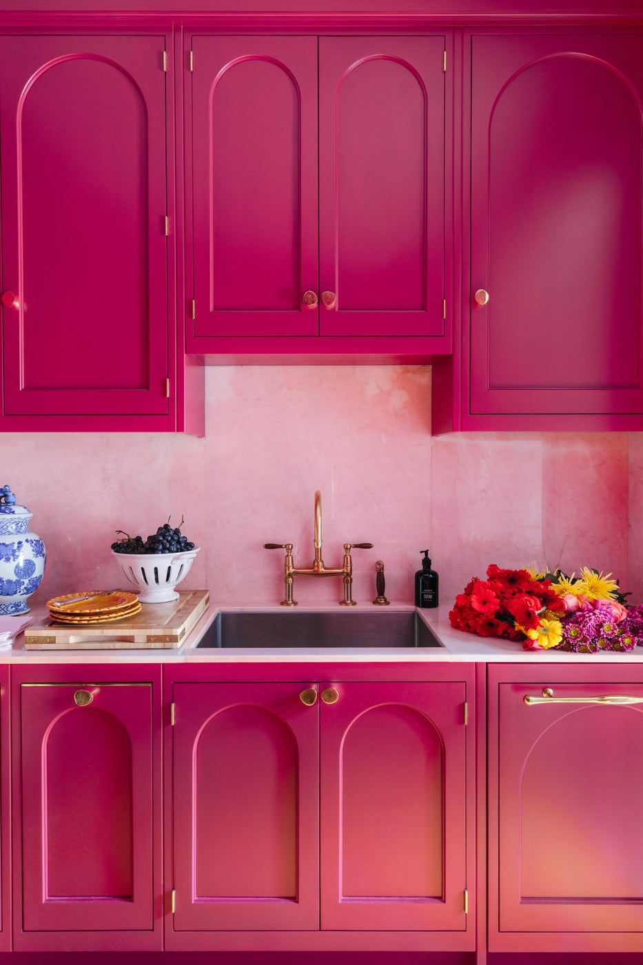 Custom Kitchen Cabinets in berry with arch detail, pink marble, & brass fixtures