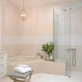 Coral bathroom with white custom cabinetry. Glass shower and vanity stool.