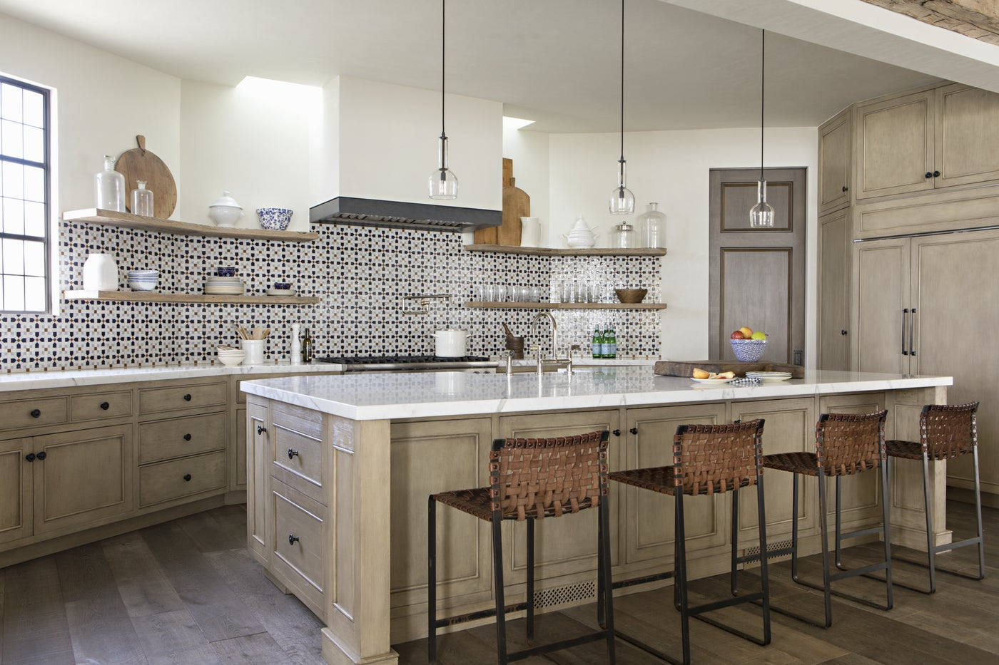 This kitchen includes Moroccan mosaic tiles and a plaster hood with steel band