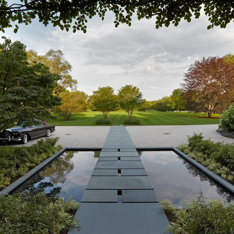 The entry to the home crosses a reflecting pool surrounded by planting.