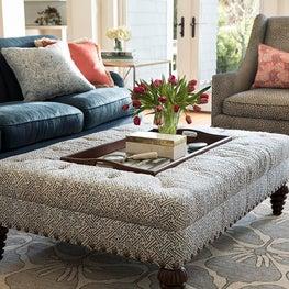Interior living room with geometric upholstered tray ottoman/ indigo blue sofa