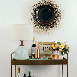 Welcoming bar cart with custom porcupine mirror and mid-century table lamp