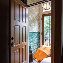 Entry with large floral wallcovering, glazed subway tile, mosaic floor tile.