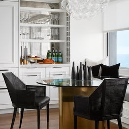 Breakfast nook with antique mirror backsplash, bubble chandelier and brass table base.