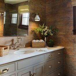 Warm modern farmhouse bathroom with brass accents, warm brown wallpaper
