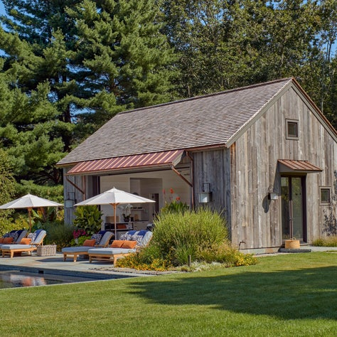 Antique barn siding is contrasted by crisp copper overhangs on this Connecticut pool house.